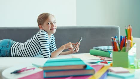 Girl-Lying-On-The-Sofa-And-Using-Cell-Phone