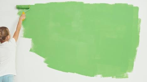Niña-Pintando-Pantalla-Verde-En-La-Pared-Y-Sonriendo-A-La-Cámara