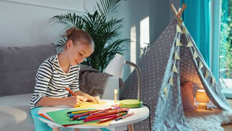 Girl-Paints-Using-With-Pencils-In-Notebook-At-The-Table