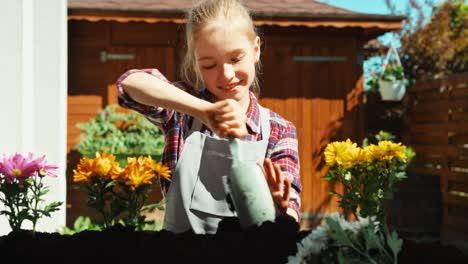 Niña-Plantando-Flores-Amarillas-Al-Suelo-Y-Sonriendo-A-La-Cámara