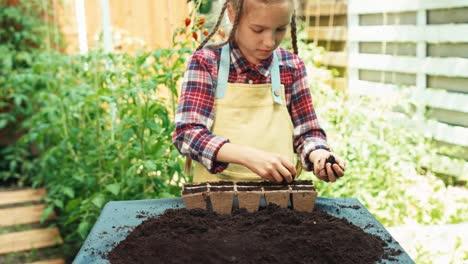 Girl-Preparing-Soil-In-Pots-For-Seeds