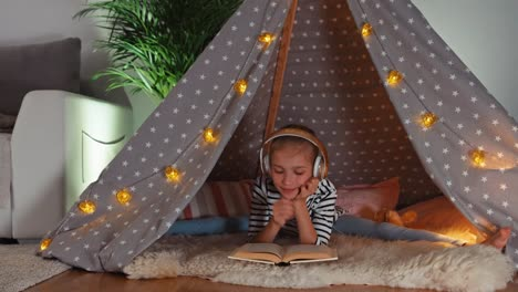 Girl-Reading-Book-And-Listening-Music-In-Wigwam