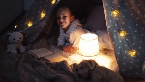 Niña-Leyendo-Un-Libro-Acostado-En-Wigwam-En-La-Noche-Vista-Superior