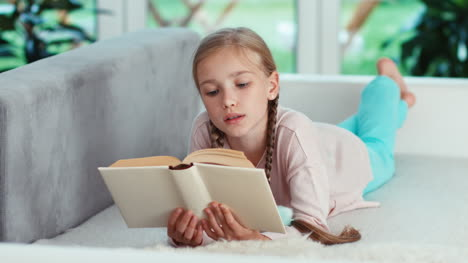 Girl-Reading-Book-Lying-On-The-Sofa