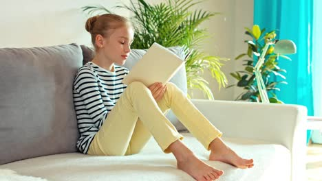 Girl-Reading-Book-On-The-Sofa-Dolly-Shot