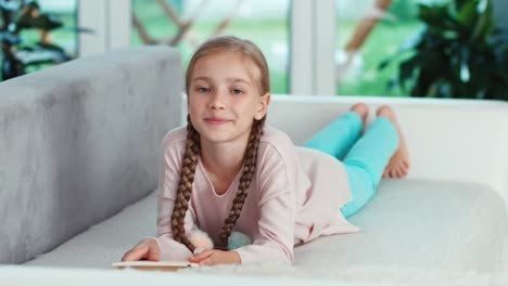 Girl-Reading-Book-Child-Lying-On-The-Sofa-In-The-Living-Room