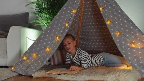 Girl-Relaxing-In-Wigwam-Child-Reading-Book-And-Smiling-At-Camera