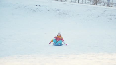 Girl-Rides-A-Sledding-Down-On-Snow-Disk-A-Winter-Hill-Girl-Laughing