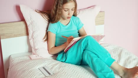 Girl-Sitting-On-Bed-Writing-In-Notebook-And-Looking-At-Camera