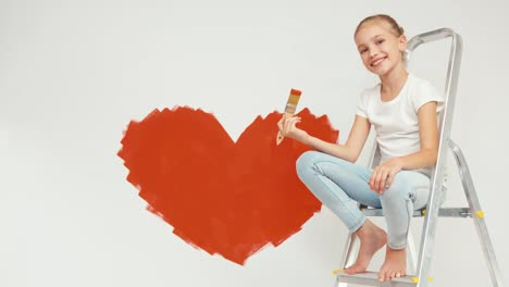 Girl-Sitting-On-The-Ladder-Holds-Paintbrush-With-Red-Paint-And-Smiling-At-Camera