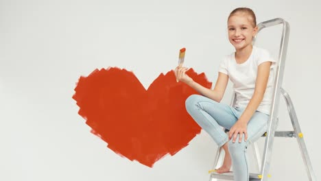 Girl-Sitting-On-The-Ladder-Holds-Paintbrush-With-Red-Paint