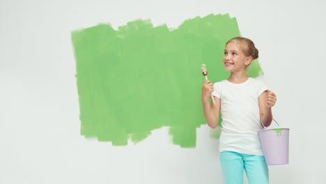 Niña-De-Pie-Cerca-De-La-Pantalla-Verde-Sostiene-El-Pincel-Con-Pintura-Y-Sonriendo