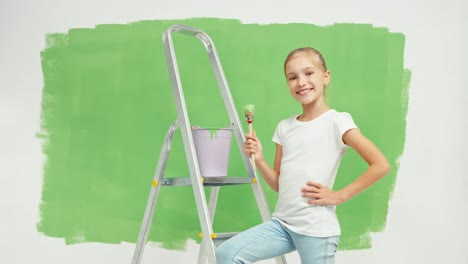 Girl-Standing-Near-Ladder-And-Holds-Paint-Brush-Against-Green-Screen