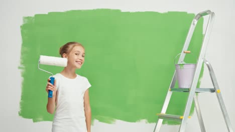 Girl-Turns-At-Camera-And-Holds-Paint-Brush-Near-Green-Screen