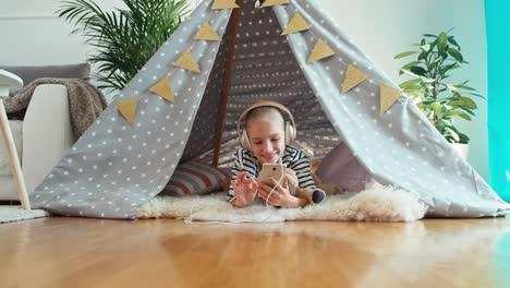Chica-Usando-Teléfono-Celular-Escuchando-Música-En-Auriculares-Y-Sonriendo-A-La-Cámara