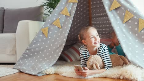 Girl-Using-Cell-Phone-Child-Lying-In-The-Wigwam