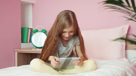 Niña-Usando-Tableta-Y-Mirando-A-Otro-Lado-Y-Riéndose-De-La-Cámara