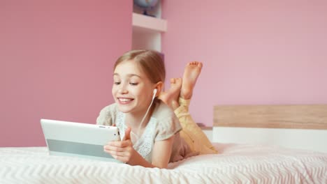 Girl-Using-Tablet-PC-And-Laughing-Child-Lying-On-The-Bed