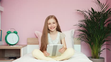 Girl-Using-Tablet-When-Sitting-In-Bedroom-Zooming