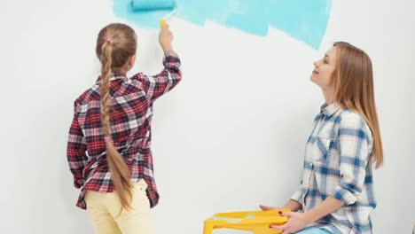 Girl-With-Her-Mother-Painting-Wall-To-Blue-Color