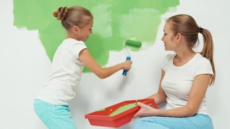 Girl-With-Mother-Painting-Wall-To-Green-Color-And-Laughing-At-Camera