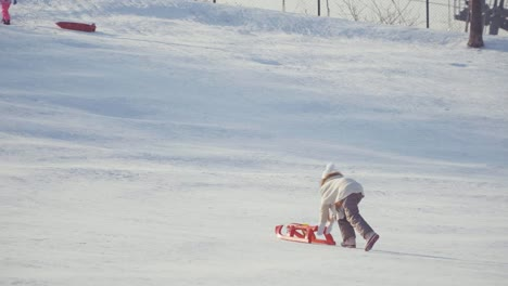Girl-With-Sled-On-Snow-Hill-In-Sunny-Day
