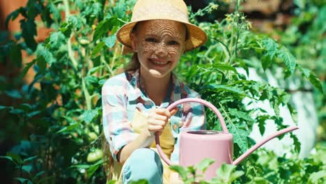 Girl-With-Watering-Can-In-The-Kitchen-Garden-And-Smiling-At-Camera