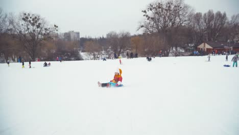 Happy-Child-Girl-8-Years-Sitting-On-Snow-Disk-And-Sliding-Downhill-In-Wintertime