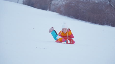 Happy-Child-Girl-Lying-On-Sled-And-Sliding-Downhill-In-Wintertime