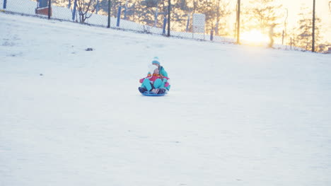 Happy-Family-Rides-A-Sledding-Down-On-Snow-Disk-In-Sunny-Day-Against-Sunset