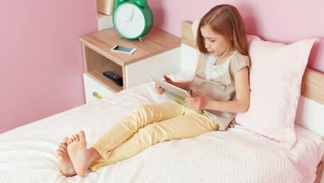Niña-Riendo-En-Auriculares-Con-Tablet-Pc-En-La-Vista-Superior-Del-Dormitorio