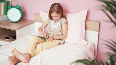 Niña-Riendo-En-Auriculares-Con-Tablet-Pc-En-El-Dormitorio