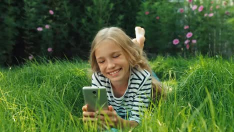 Laughing-Girl-Lying-On-Grass-With-Cell-Phone-Dolly-Shot
