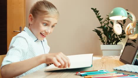 Laughing-Student-Girl-8-Aged-Reading-Book-Child-Sitting-At-The-Desk-At-Home