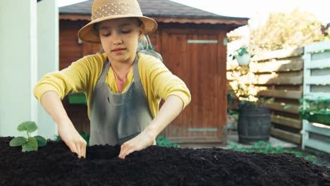 Kleines-Bauernkind-Das-Gurkensämlinge-In-Den-Boden-Pflanzt-Und-In-Die-Kamera-Lächelt