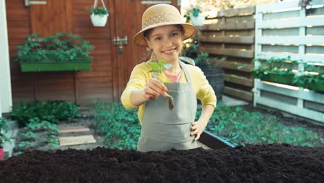 Kleines-Bauernmädchen-Das-Gurkensämlinge-In-Den-Boden-Pflanzt-Und-Lächelt