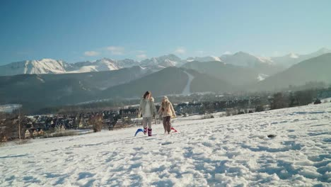 Mother-And-Child-Girl-Holds-In-Hands-Sleds-Are-Go-Against-Mountains-At-Camera