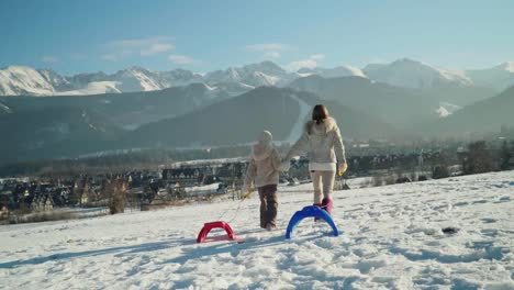 Mother-And-Child-Girl-Holds-In-Hands-Sleds-Are-Go-Against-Mountains-From-Camera