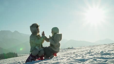Mother-And-Child-Girl-Sitting-On-Sled-In-Sunny-Winter-Day-In-Mountains