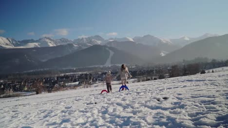 Mother-And-Child-Girl-With-Sleds-Running-And-Dancing-Against-Mountains-At-Camera