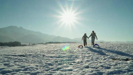 Mother-And-Child-Girl-With-Sleds-Running-To-Sun-In-Mountains