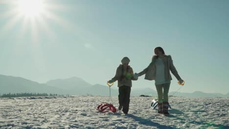 Mother-And-Child-Girl-With-Sleds-Walking-In-Sunny-Winter-Day-In-Mountains