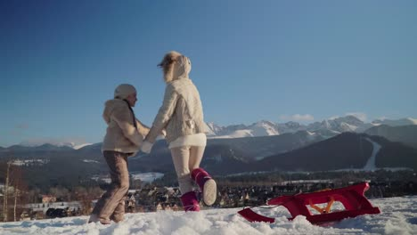 Mother-And-Daughter-Have-Fun-In-Mountains-Girls-Dancing-In-Sunny-Winter-Day