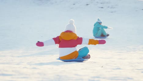 Mother-And-Daughter-Have-Fun-On-Winter-Hill-Family-Rides-A-Sledding-Down-On