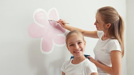 Madre-E-Hija-Pintando-Flores-En-La-Pared-Y-Sonriendo-A-La-Cámara