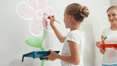 Mother-And-Daughter-Painting-Flower-On-The-Wall-In-Bedroom