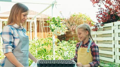 Mother-And-Daughter-Planning-Planting-Seeds-To-Soil-And-Smiling-At-Camera
