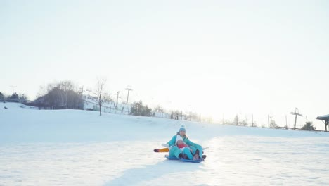 Mother-And-Daughter-Rides-A-Sledding-Down-On-Snow-Disk-A-Winter-Hill-At-Camera