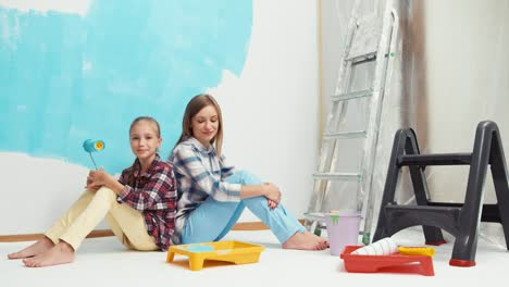 Mother-And-Daughter-Sitting-On-The-Floor-After-Painting-The-House