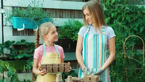 Mother-Giving-Child-Two-Peat-Pots-In-Kitchen-Garden-Cheerful-Little-Farmer